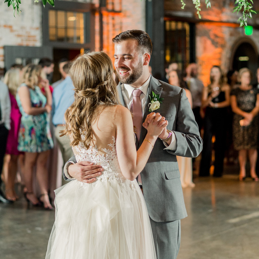 groom smiling at bride during first dance