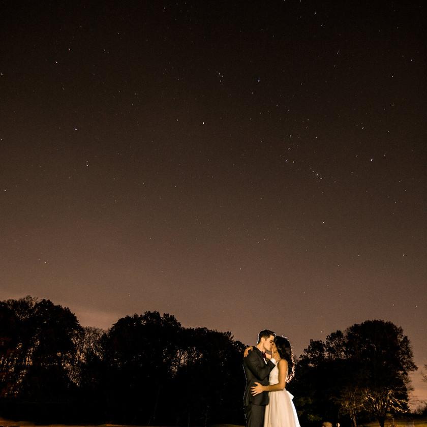 bride and groom pose under night sky