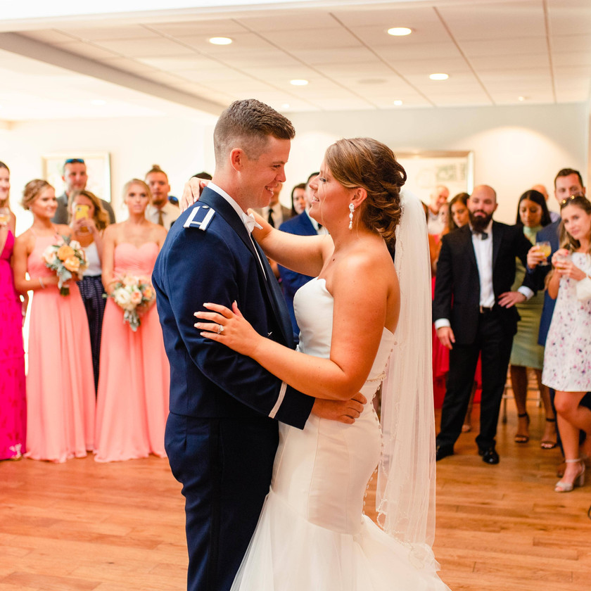 bride and groom first dance while guests stand around and watch