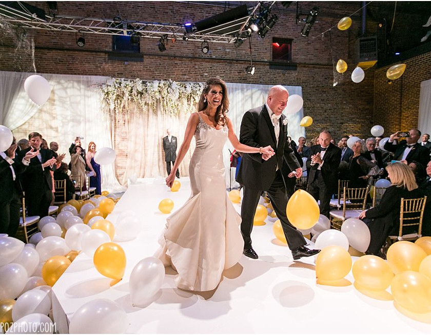 bride and groom walk out of ceremony with balloons dropped everywhere