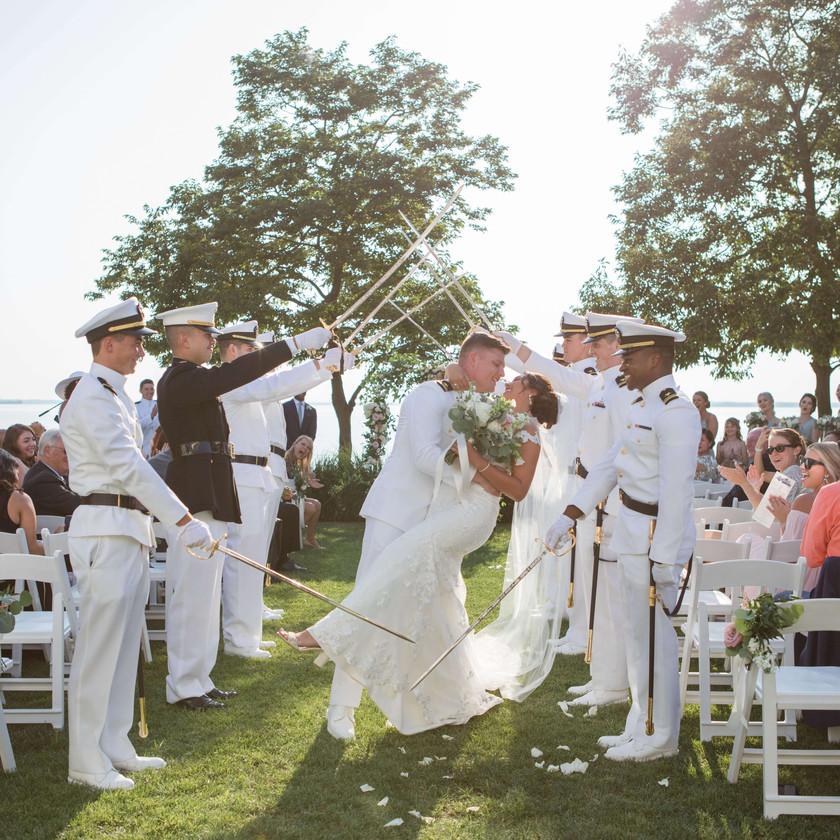 groom dips bride on ceremony exit underneath navy officers sabres