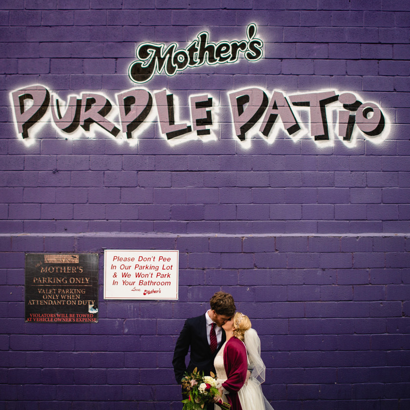 bride and groom kiss in front of purple wall
