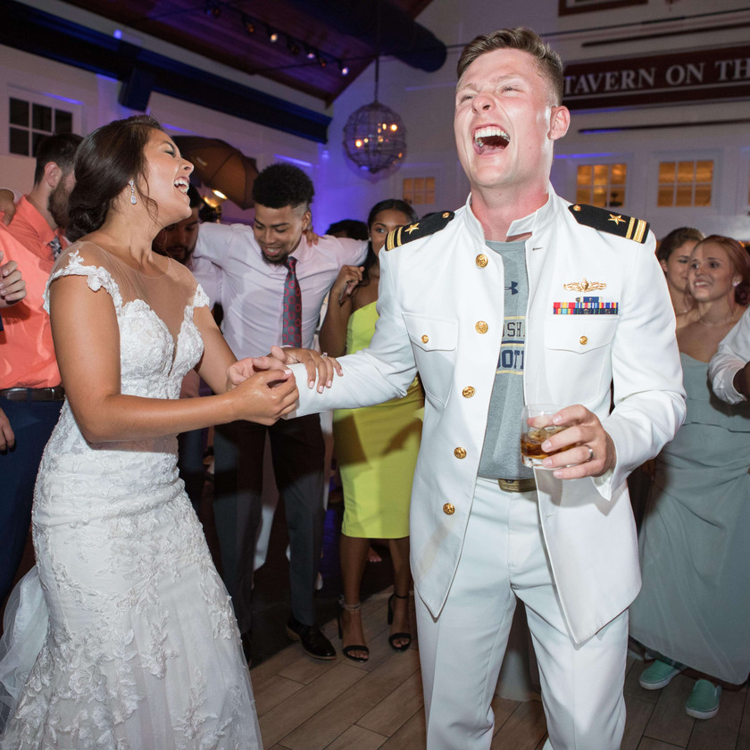bride and groom surrounded by friends on dance floor