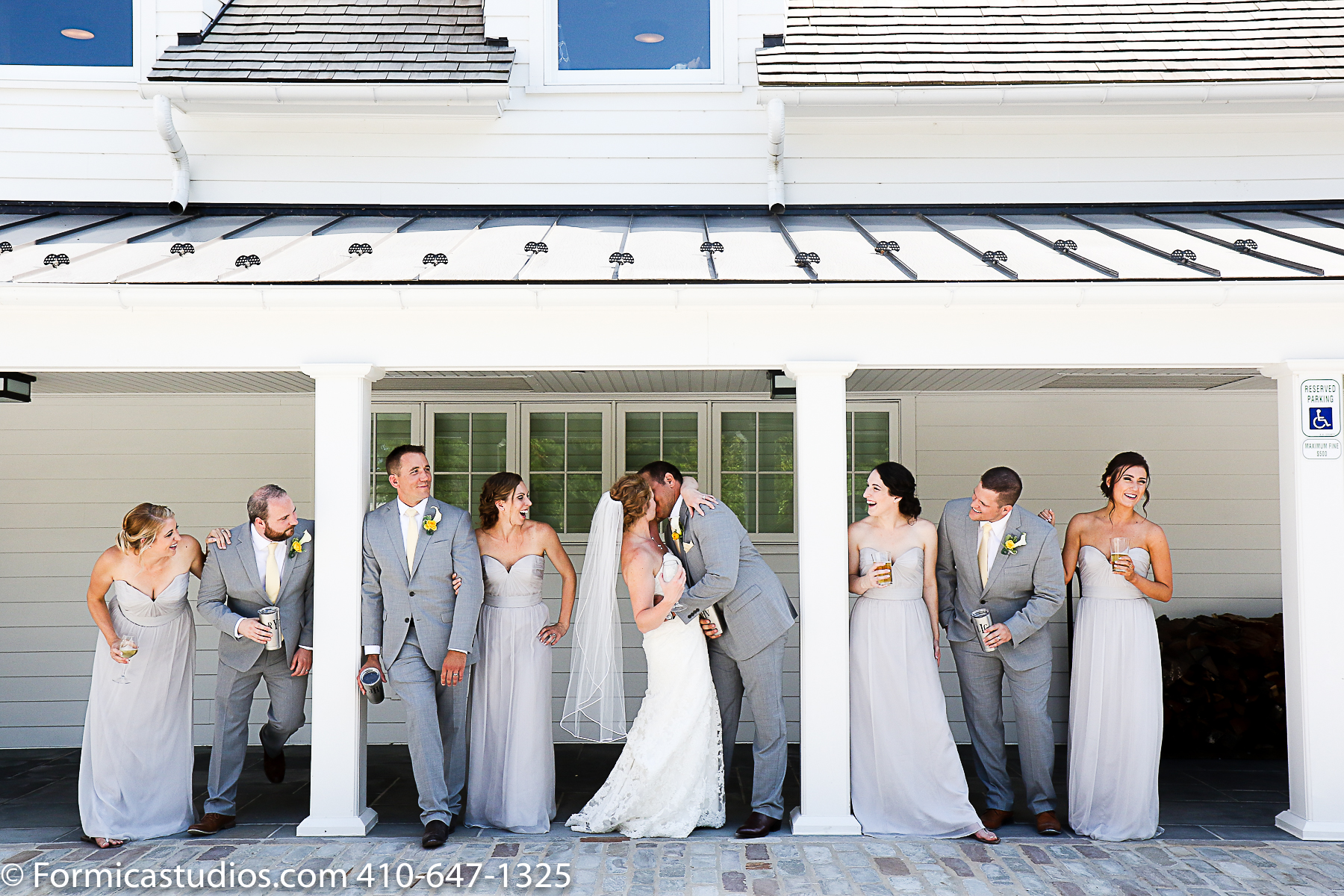 bride and groom kiss under awning while wedding party watches