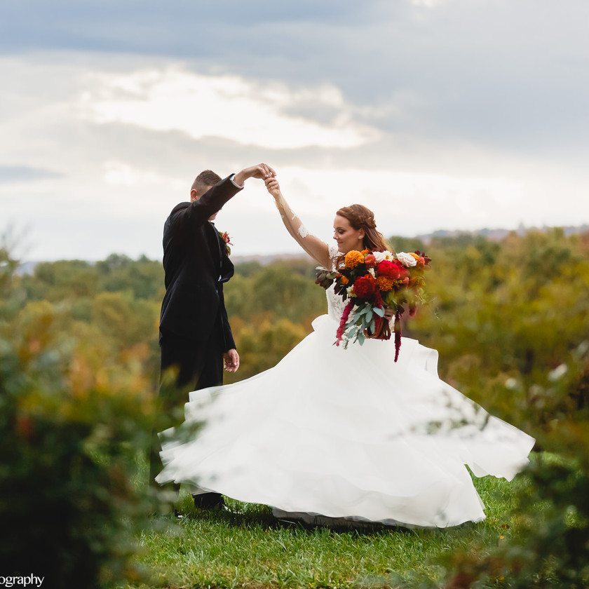 groom spinning bride in field