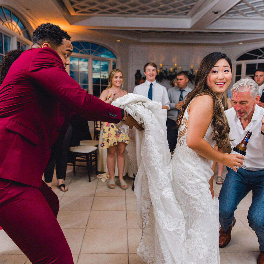 man in red suit holding up back of bride's dress while dancing
