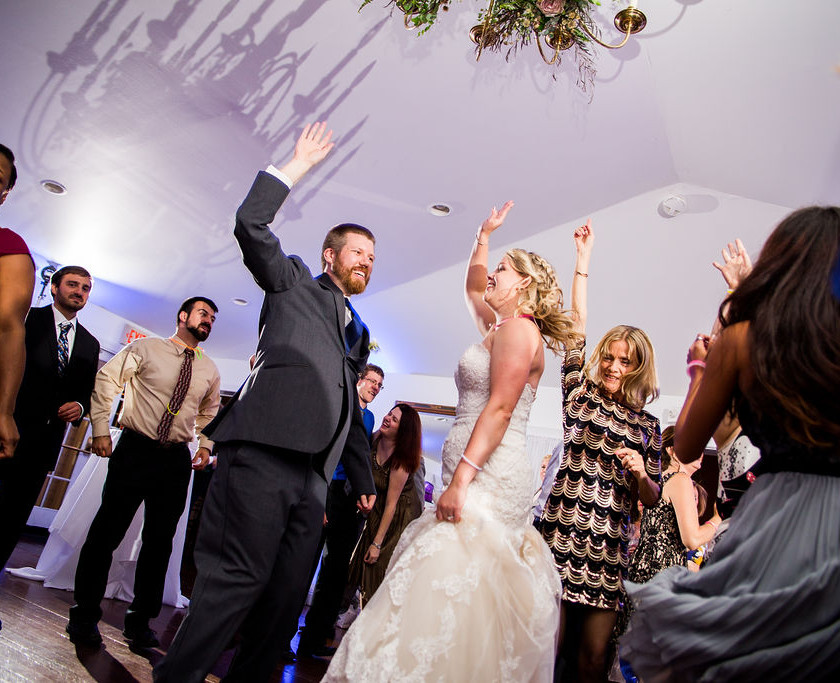 bride and groom dance with hands up