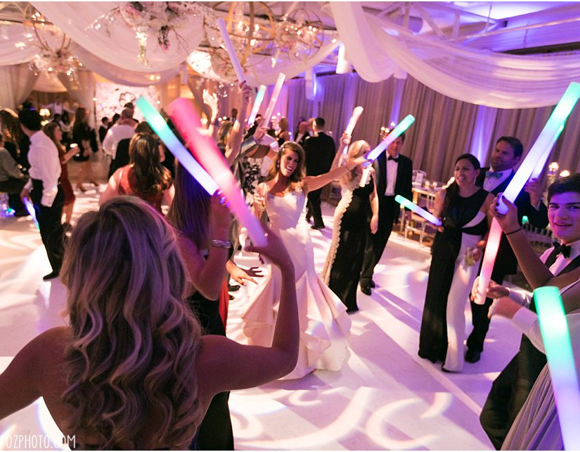 wedding guests hold light tubes while partying