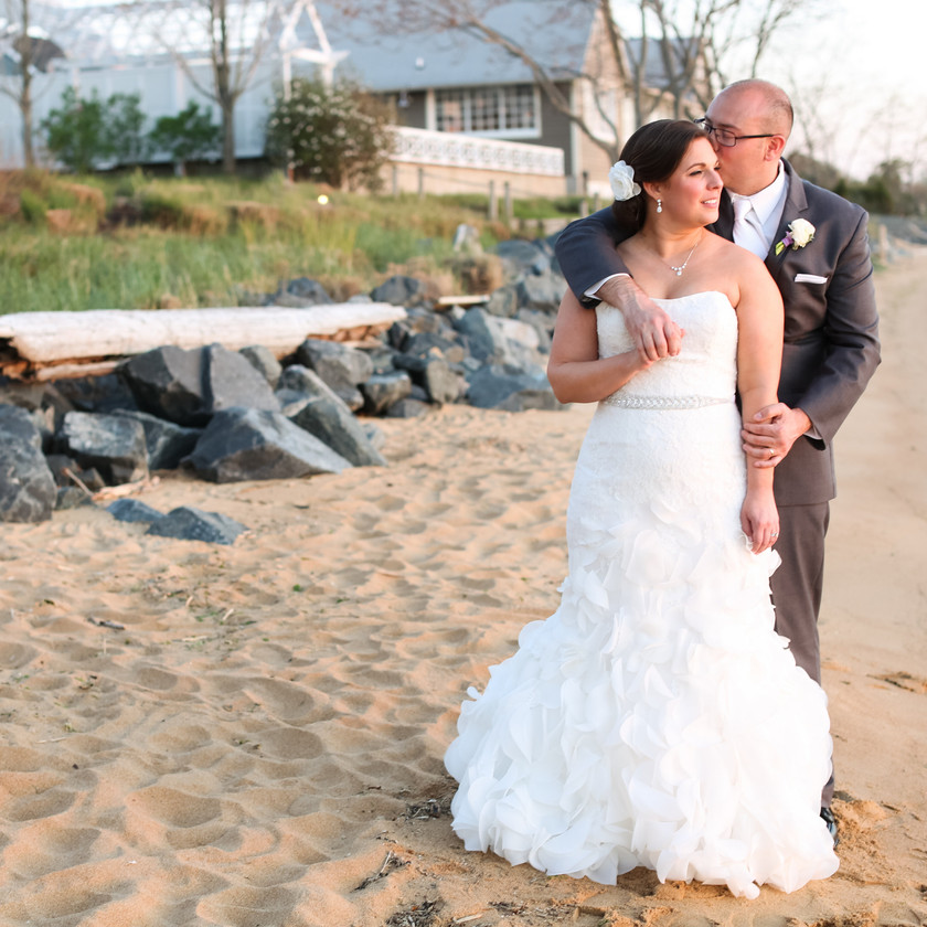 groom kisses brides head while on beach