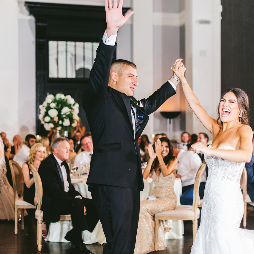 groom and bride hold up hands on dance floor