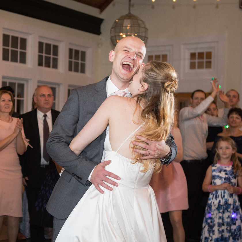 groom laughs while dancing with bride