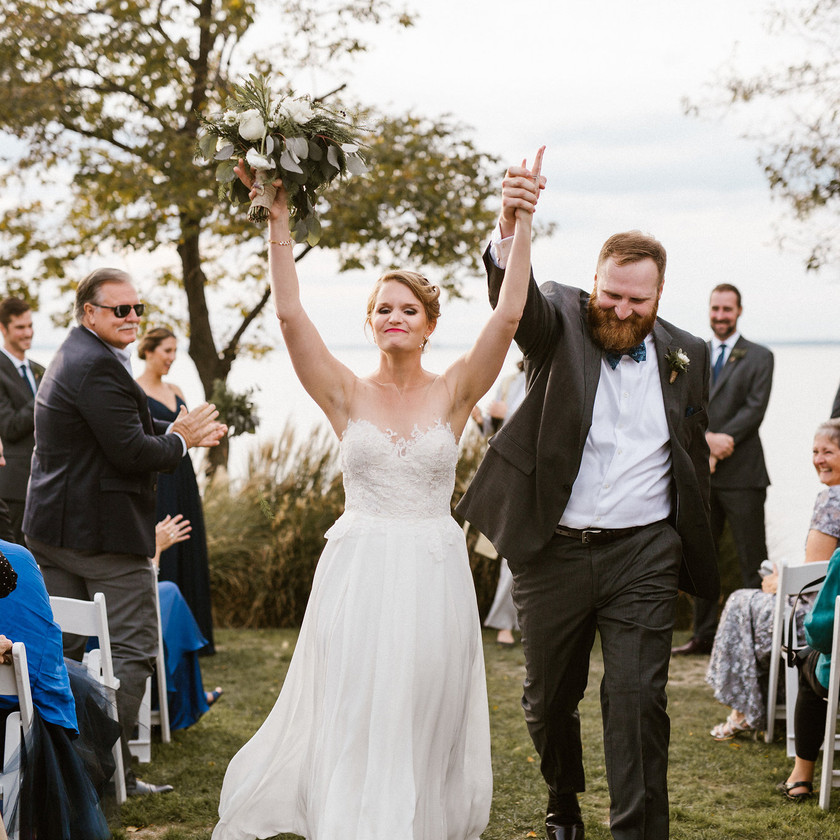 bride and groom exit ceremony with hands up