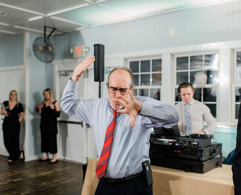 older gent wearing red tie dancing at wedding in front of dj