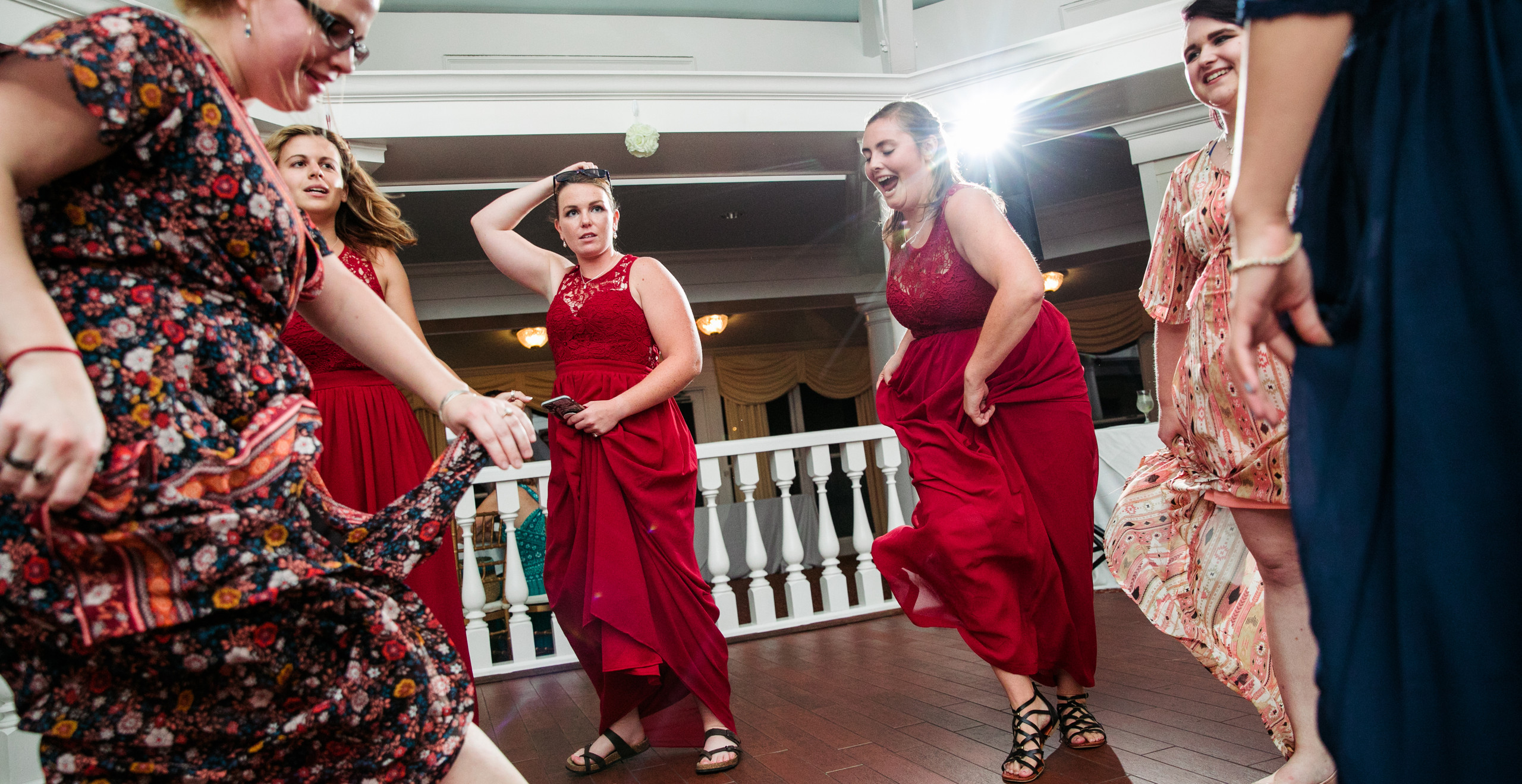 bridesmaids in red dresses dance