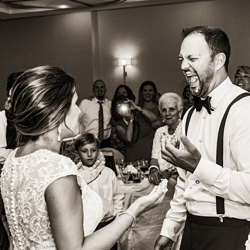 bride and groom laugh while feeding cake to each other