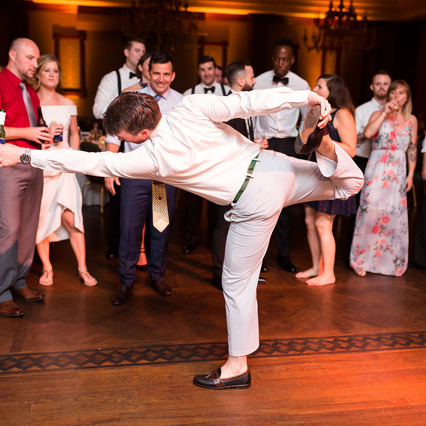 man dancing on one leg and holding other up at wedding