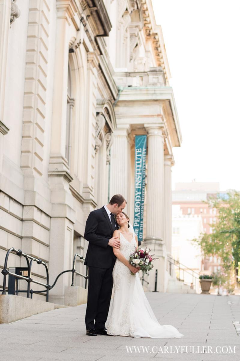 groom kissing bride outside building