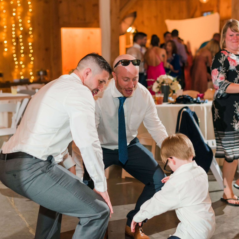 guys dancing with young boy at wedding