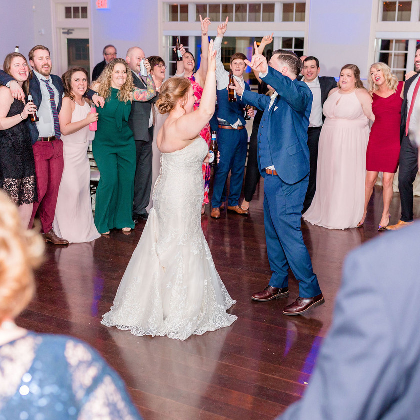 bride and groom dance with hands up and guests surround them