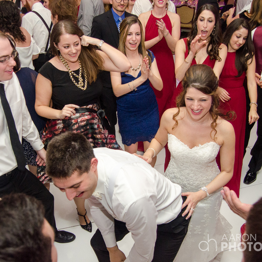 groom dances in front of bride with guests around