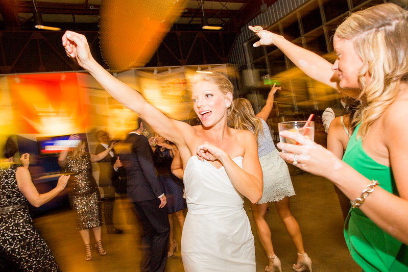 bride has hands up while dancing