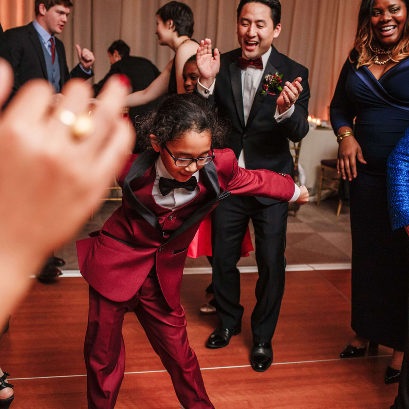 young boy in red suit floss dancing at wedding while guests clap