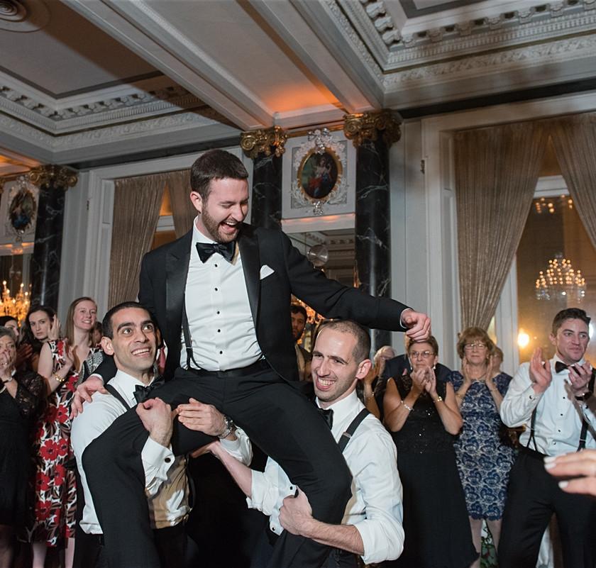 groomsmen lift up groom on their shoulders