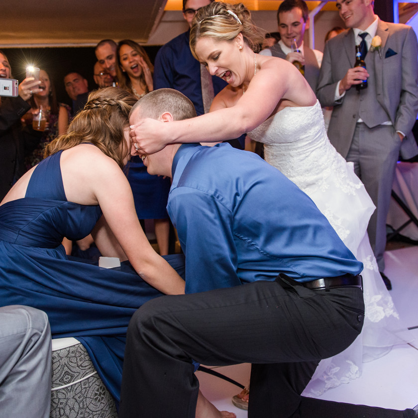 bride covering eyes of guy while he puts garter on woman