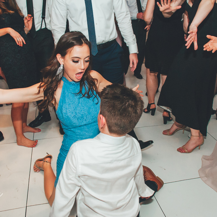 girl in turquoise dress dancing with kid
