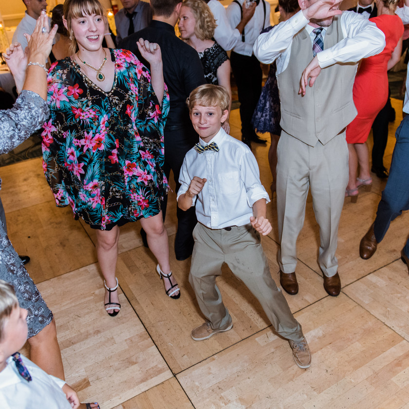 young boy and guests dance at wedding