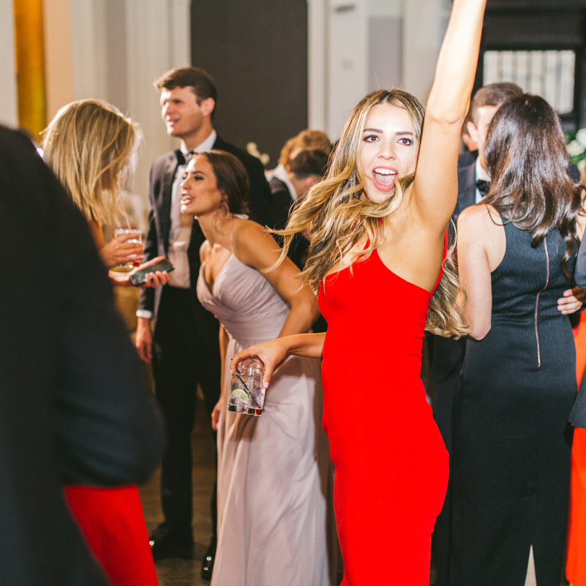 woman in red dress dances with arm up