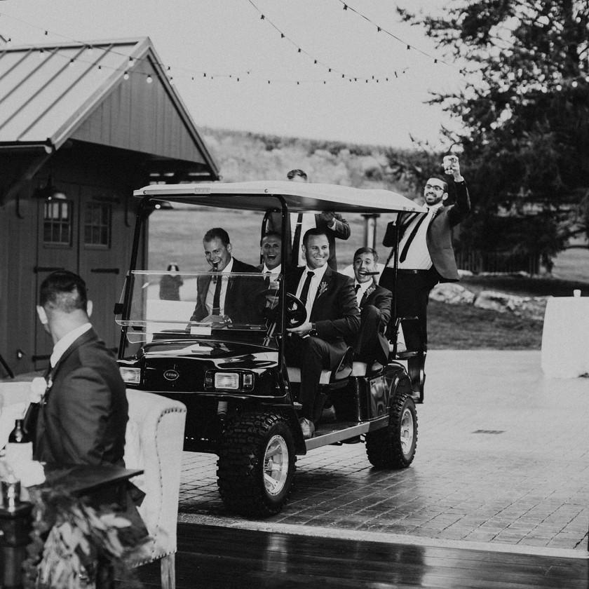 bride and groom look behind their table and see groomsmen drive up in golfcart
