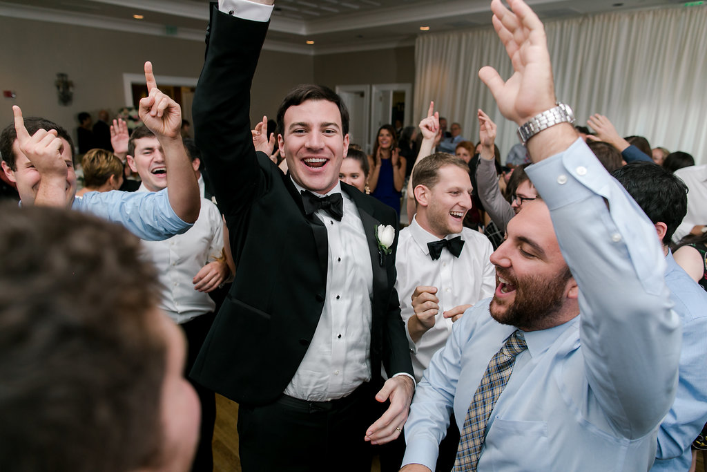 groom and guys dancing with hands up