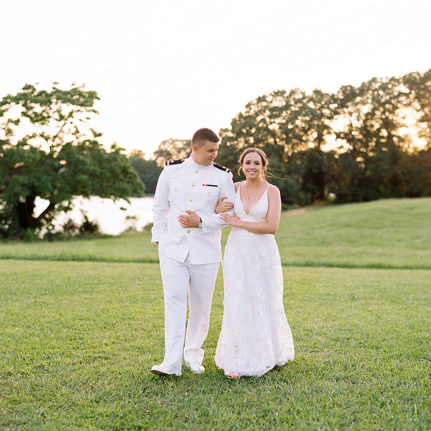 bride and groom walk on lawn during sunset