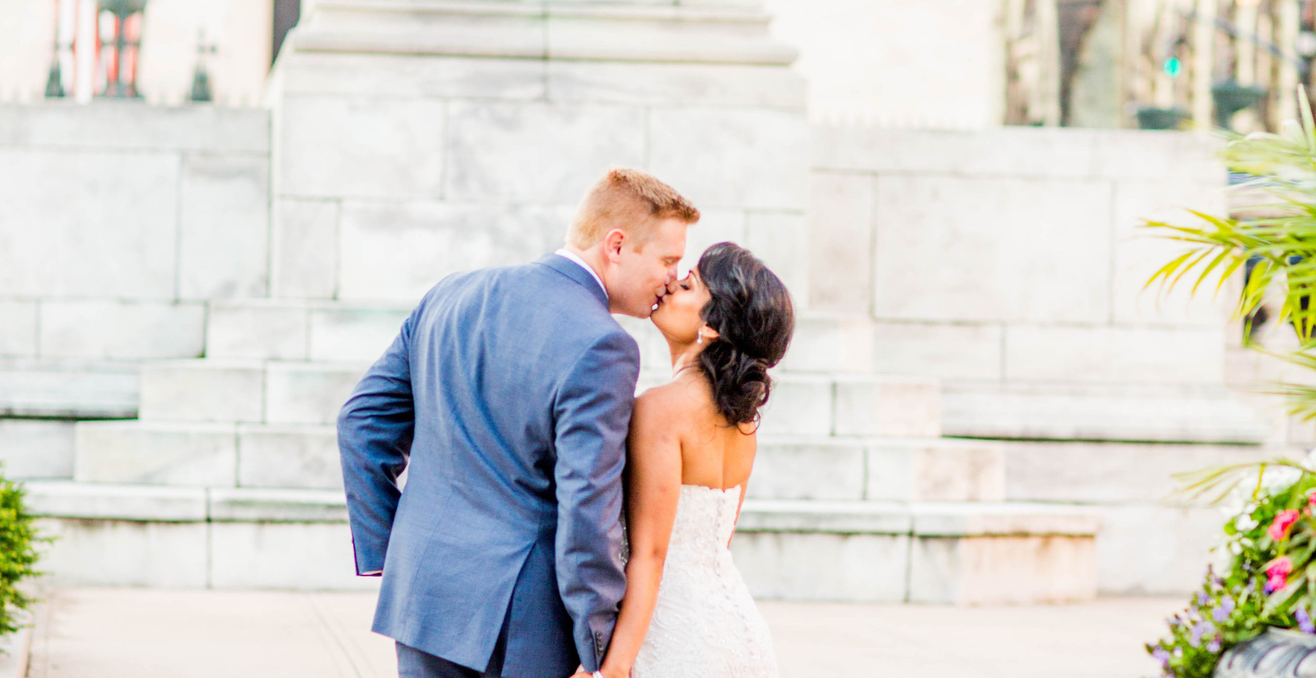 bride and groom kissing by a statue