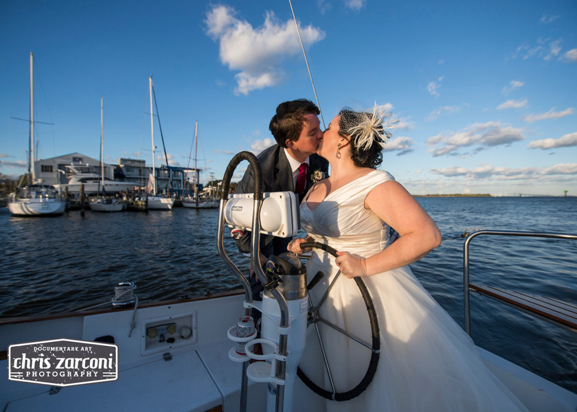 bride and groom kissing while steering boat