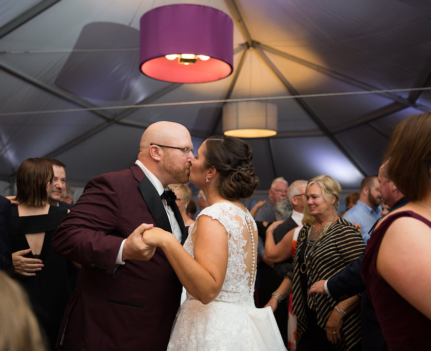 bride and groom kiss while slow dancing