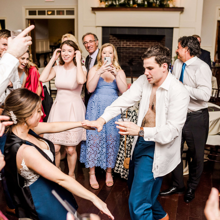 bride dances with groom while wearing his vest