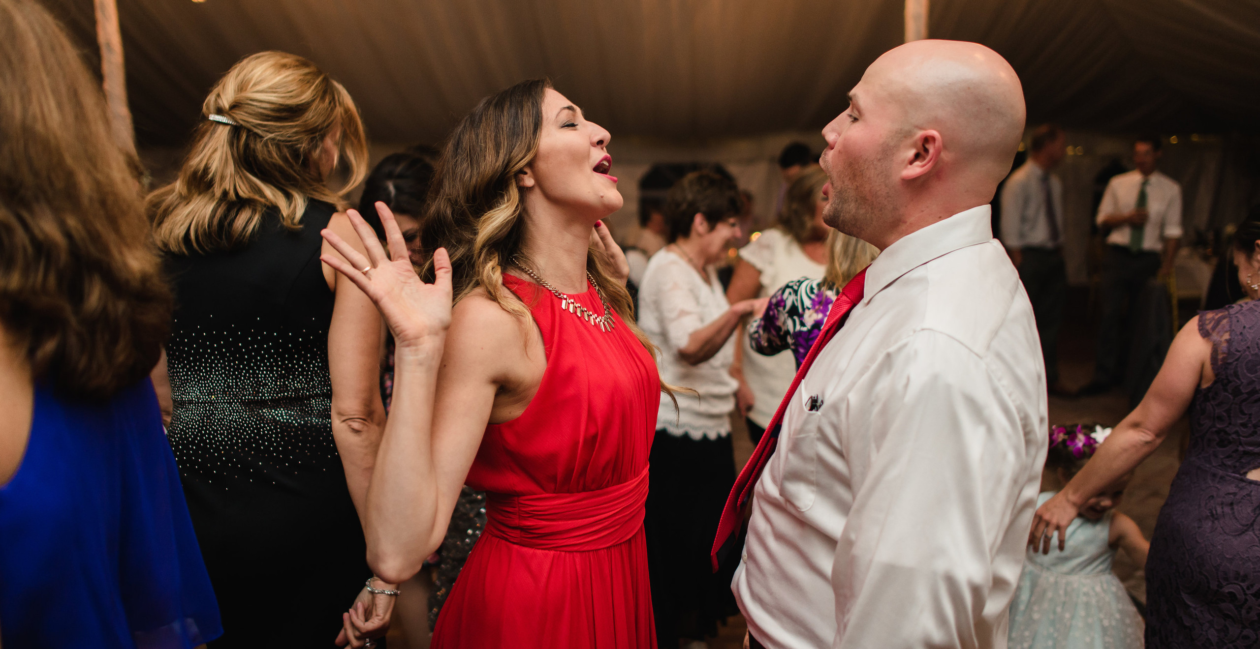 woman in red dress dancing with man at wedding