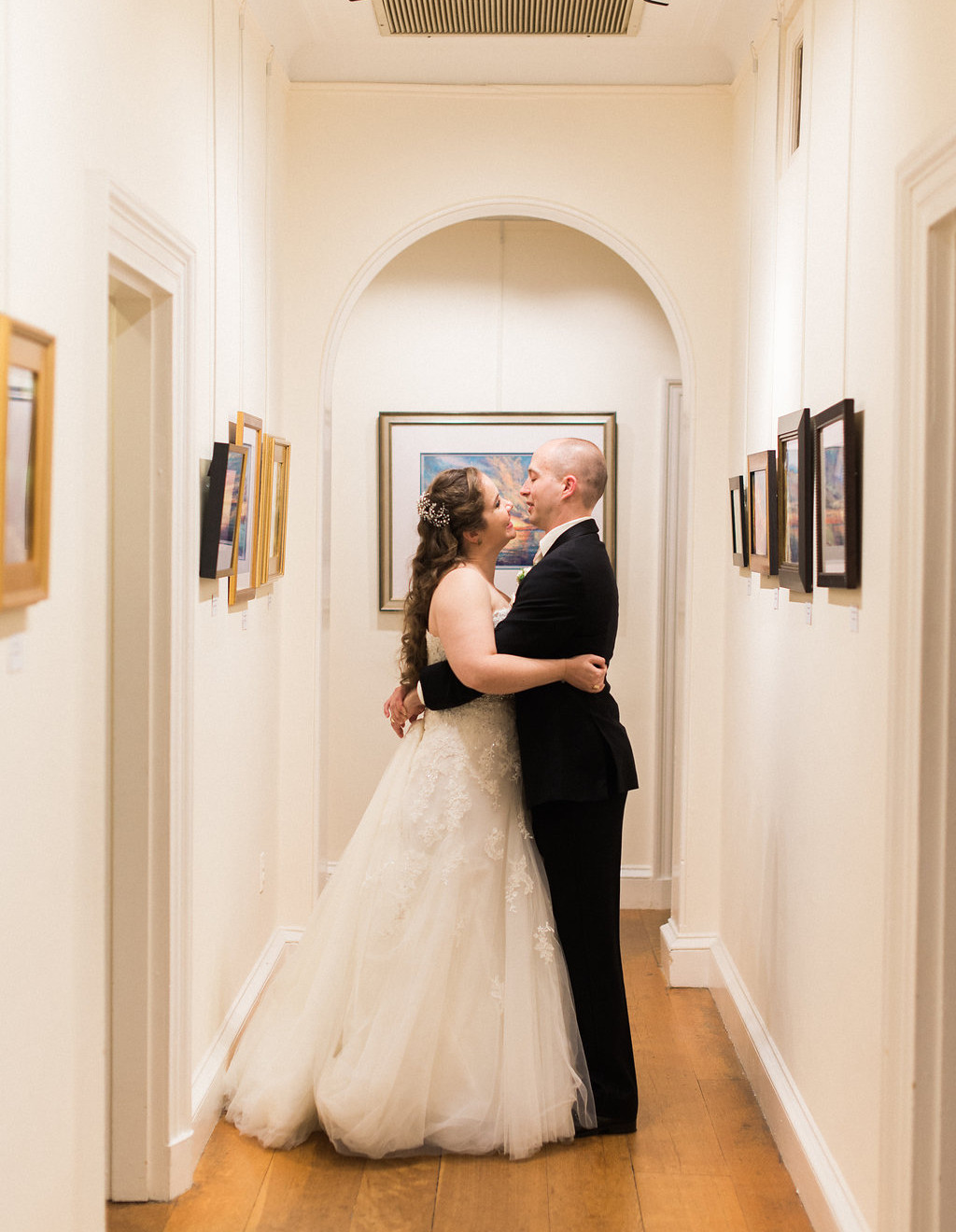 bride and groom hold each other in hallway