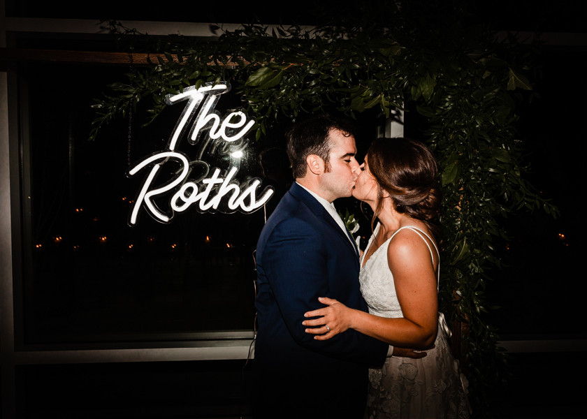 bride and groom kiss in front of neon sign