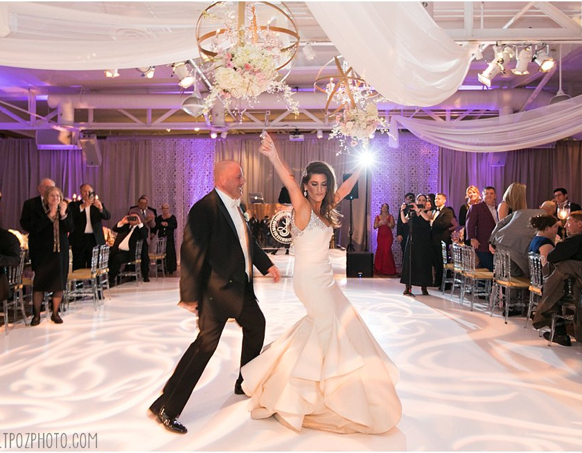 bride has hands up during first dance