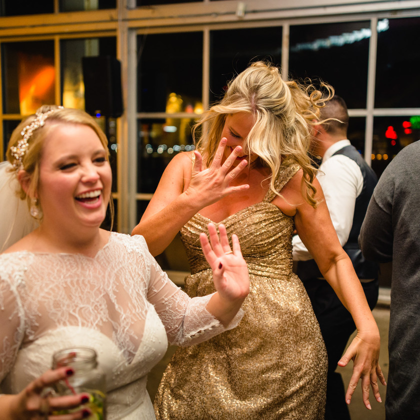 bride and friend in gold dress dancing