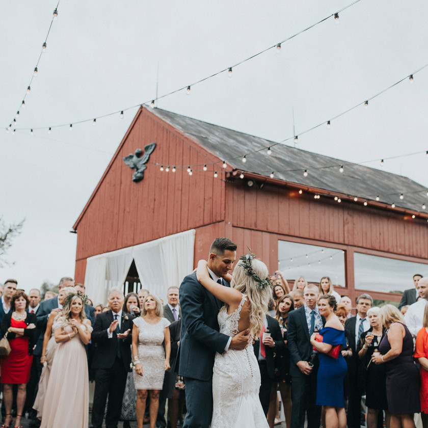 bride and groom first dance outside barn surrounded by friends