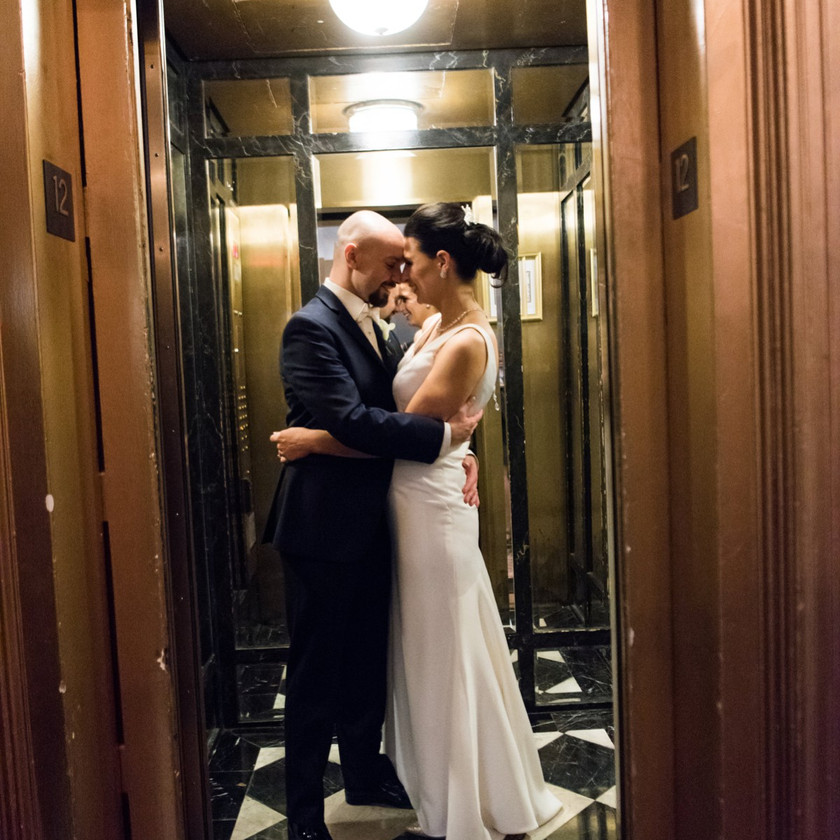 bride and groom pose in elevator