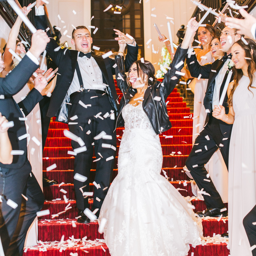 bride and groom walk down staircase covered in confetti