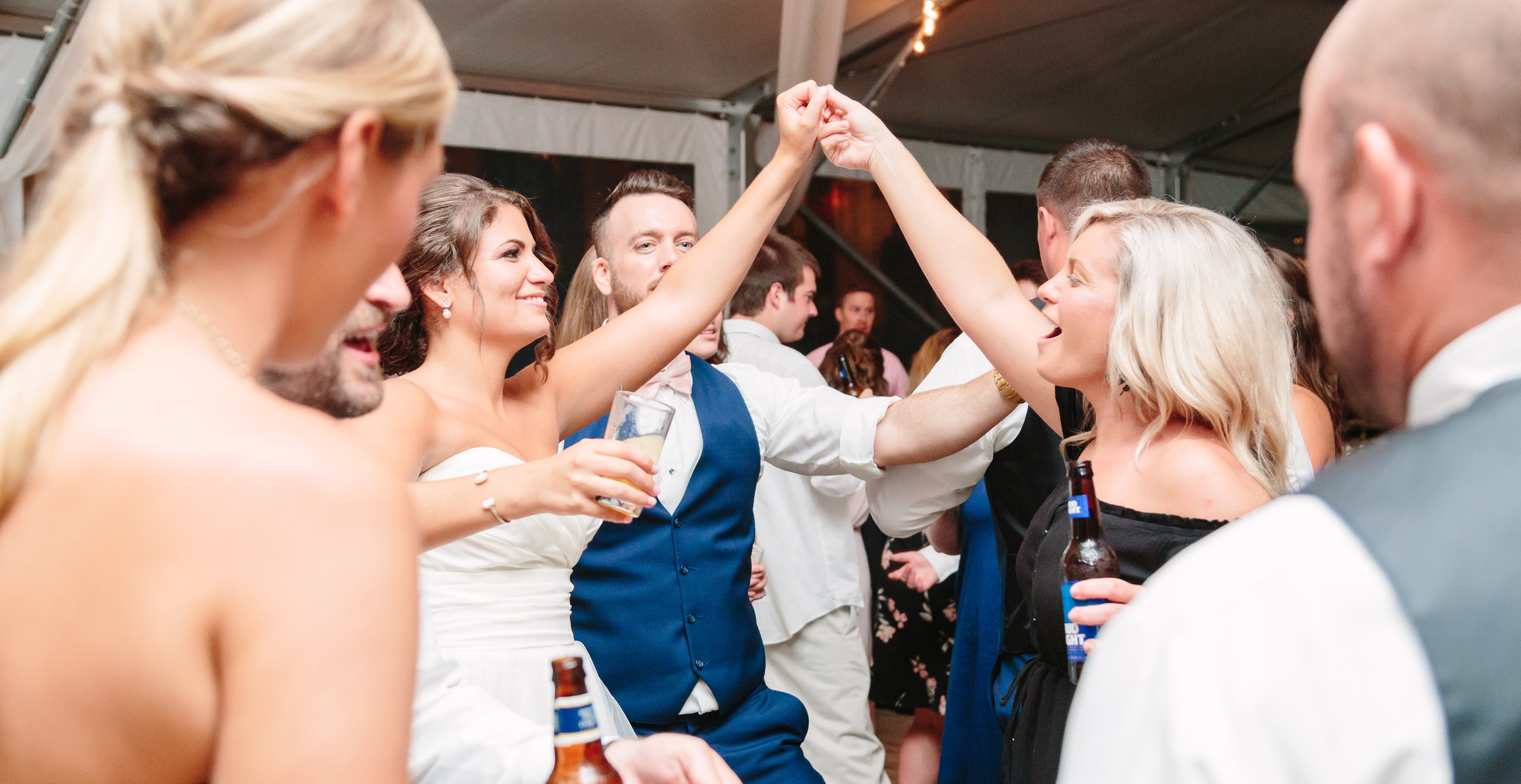 bride and guest holding hands up while dancing