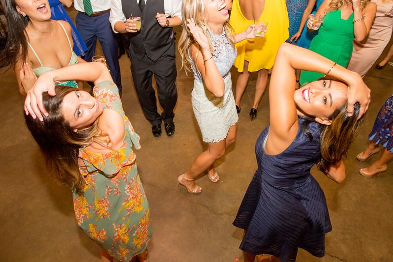 women pose while dancing at wedding