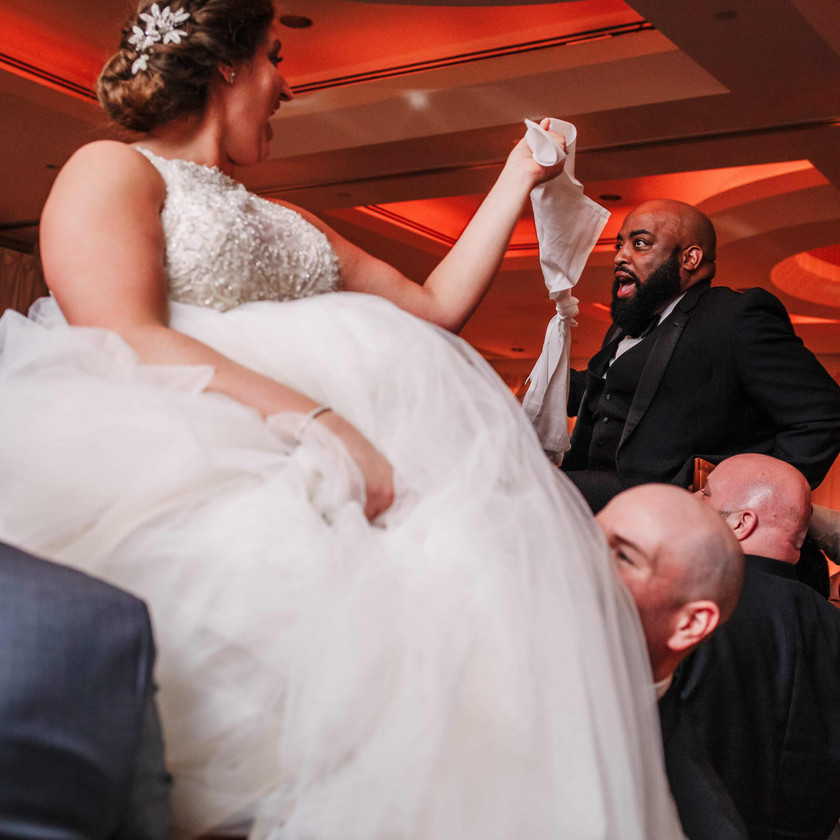 bride and groom up in chairs for hora holding a napkin between them