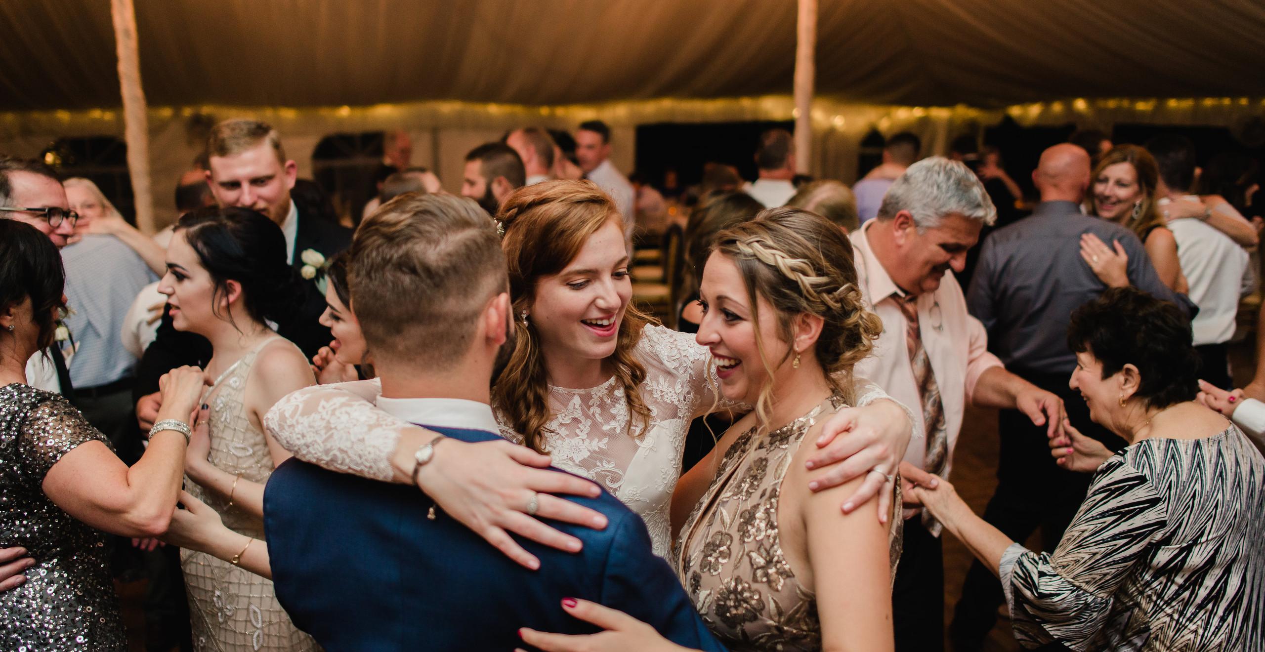 bride hugging friends at wedding while dancing